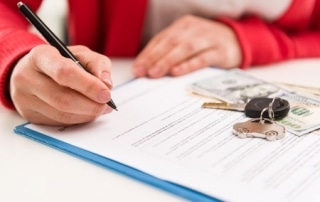 39619465 - closeup of woman auto dealer signing rental contract in the office. car key and money on papers. shallow depth of field.