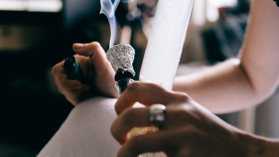 .smoking Marijuana With A Bong Close-up . Legalization And Depen