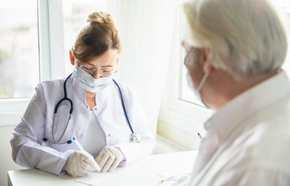 Corona-Pandemie - Tragen Mund-Nase-Bedeckung in Arztpraxis