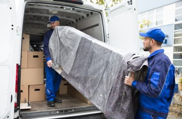 Two,Young,Delivery,Men,In,Uniform,Unloading,Furniture,From,Vehicle