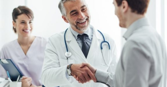 Smiling,Doctor,At,The,Clinic,Giving,An,Handshake,To,His